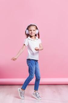 Dziewczyna słucha muzyki w hełmofonach taniec. śliczne dziecko cieszy się szczęśliwą muzyką taneczną, zamyka oko i uśmiecha się pozować