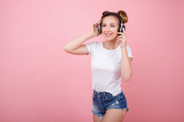 Dziewczyna słucha muzyki w słuchawkach na różowej przestrzeni