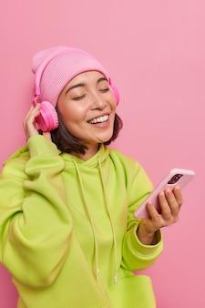 Dziewczyna słucha ulubionej muzyki trzyma oczy zamknięte od przyjemności trzyma telefon komórkowy słuchawki bezprzewodowe na uszach ubrana w zieloną bluzę i kapelusz pozuje na różowej ścianie