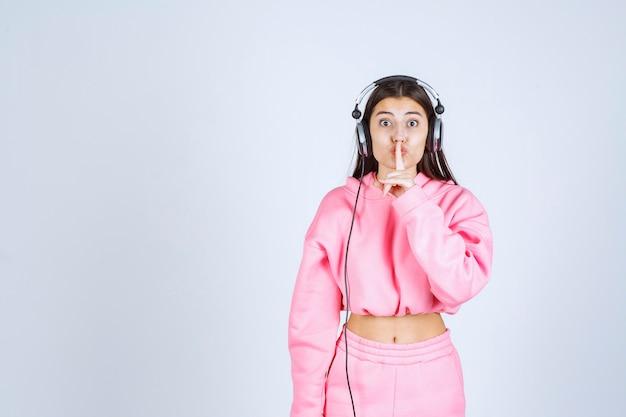Dziewczyna słuchając słuchawek i prosząc o ciszę. wysokiej jakości zdjęcie