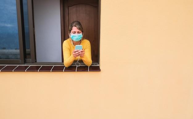 Dziewczyna słuchająca muzyki z aplikacją telefonu noszącą maskę ochronną w oknie domu - młoda kobieta podczas kwarantanny izolacji w celu zapobiegania covidowi 19 - koncepcja zdrowia i koronawirusa - skup się na twarzy