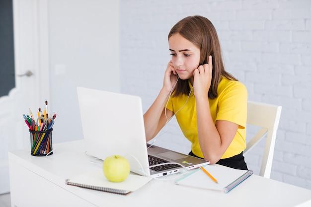 Dziewczyna słuchanie muzyki podczas odrabianiu prac domowych