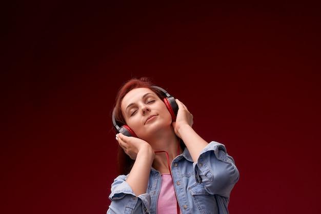 Dziewczyna, słuchanie muzyki w słuchawkach. rudowłosa młoda piękna dziewczyna w dżinsach i koszulce szczęśliwy uśmiechnięty w słuchawkach, słuchając muzyki na czerwono