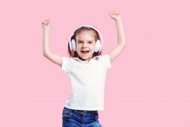 Dziewczyna, słuchanie muzyki w słuchawkach. śliczne dziecko cieszy się szczęśliwą muzyką taneczną, zamyka oko i uśmiecha się pozować