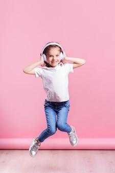 Dziewczyna, słuchanie muzyki w słuchawkach. tańcząca dziewczyna. szczęśliwa mała dziewczynka tańczy do muzyki. słodkie dziecko korzystających z szczęśliwej muzyki tanecznej.