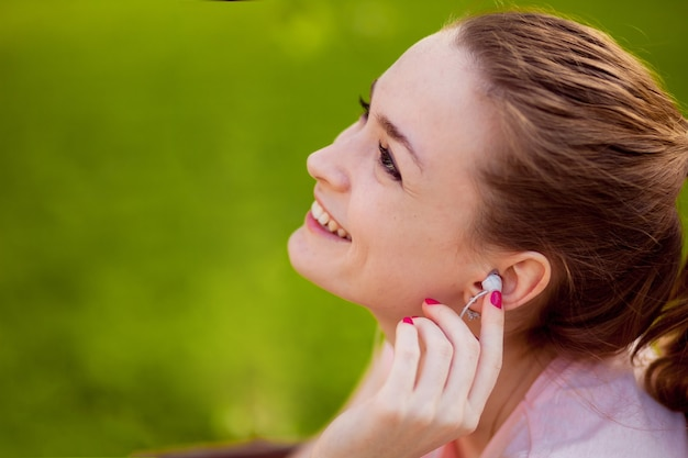 Dziewczyna, słuchanie muzyki z telefonu komórkowego w parku na ławce
