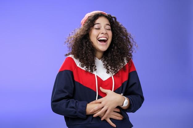 Dziewczyna słysząca zabawny, śmieszny dowcip robiący żarty z przyjaciela, śmiejącego się głośno, czując ból w brzuchu...