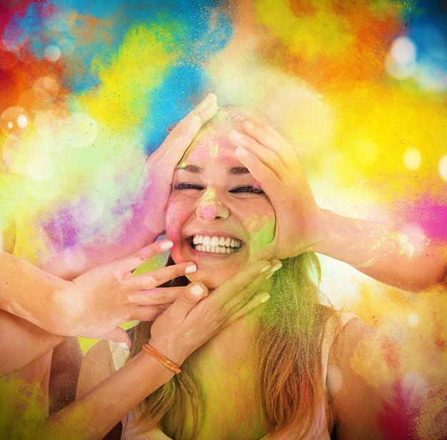 Dziewczyna śmieje się i bawi się kolorowymi proszkami