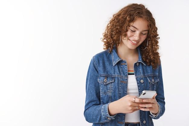 Dziewczyna śmieje się uśmiecha się rumieniąc się zadowolona czyta podnoszącą na duchu zabawną wiadomość trzymając smartfon wygląd wyświetlacz urządzenia rozbawiony szczerząc się radośnie, korzystaj z mediów społecznościowych przeglądaj internet, oglądaj ciekawe filmy online