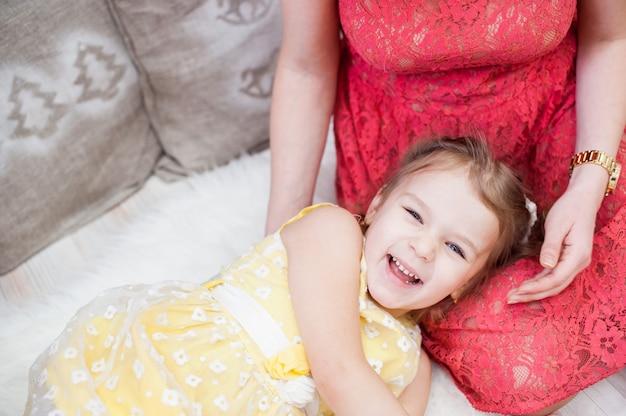 Dziewczyna śmieje się wesoło, leżąc na kolanach matki