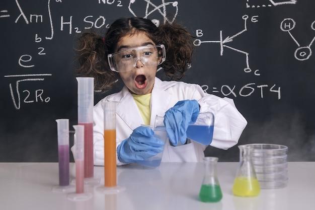 Dziewczyna śmieszne naukowiec mieszania kolb chemicznych