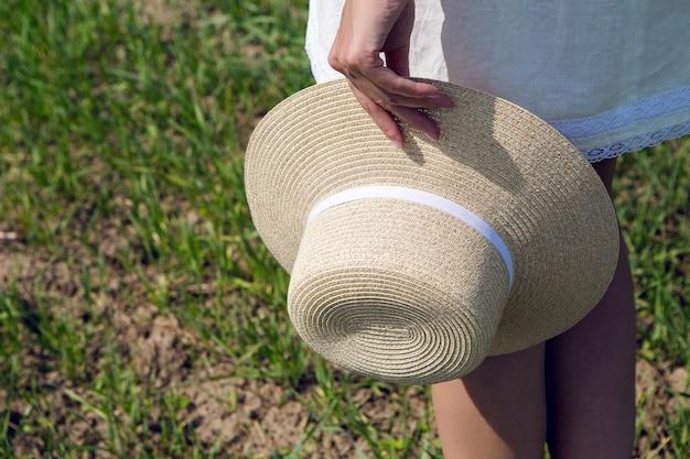 Dziewczyna spaceru w zielonym polu w białej krótkiej sukience i trzyma w prawej ręce słomkowy kapelusz. kręcony w ruchu na modelu