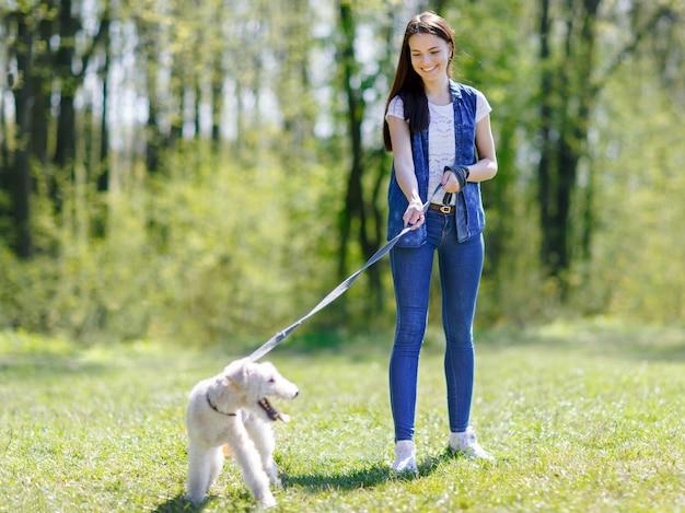 Dziewczyna spaceru z psem na smyczy w letnim parku