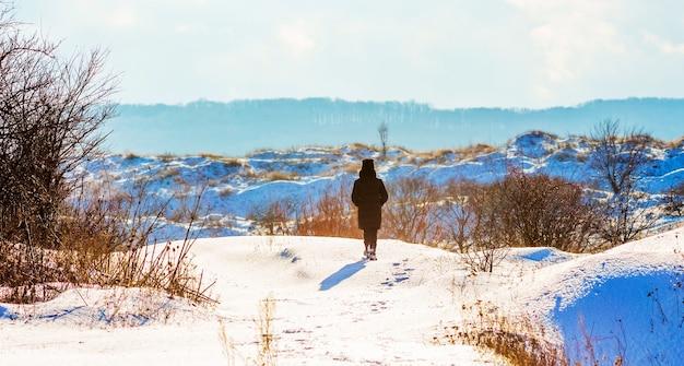 Dziewczyna spacerująca po zaśnieżonym terenie. dziewczyna zimą w przyrodzie_