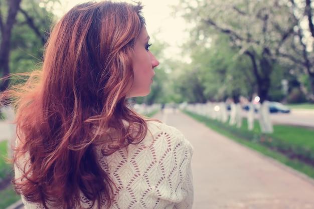 Dziewczyna spacerująca w wiosennej alei jabłek