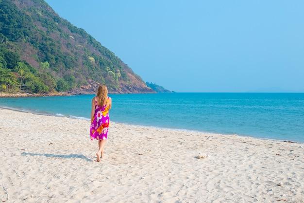 Dziewczyna spaceruje piaszczystym brzegiem morza na tropikalnej wyspie, widok z tyłu, rekreacja i turystyka w azji