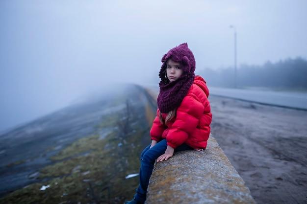 Dziewczyna spaceruje samotnie po drodze w mglisty wiosenny dzień, niepewność i czekamy na koncepcję