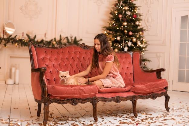 Dziewczyna spędza święta bożego narodzenia ze swoim kotem.