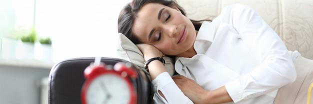 Dziewczyna śpi po pracy kanapa, stół budzik