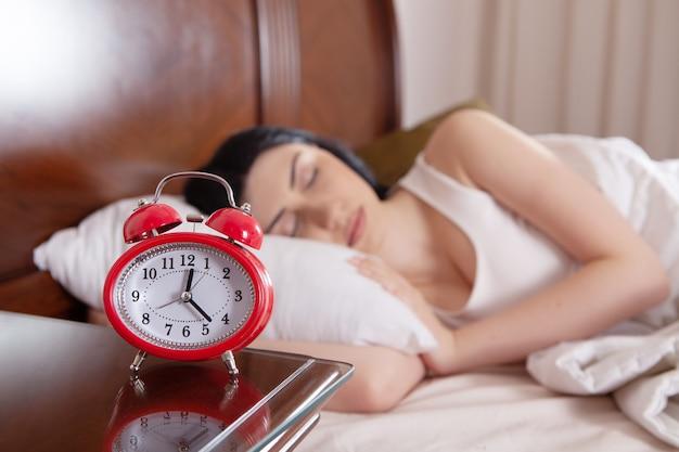 Dziewczyna śpi w łóżku i ustawia alarm