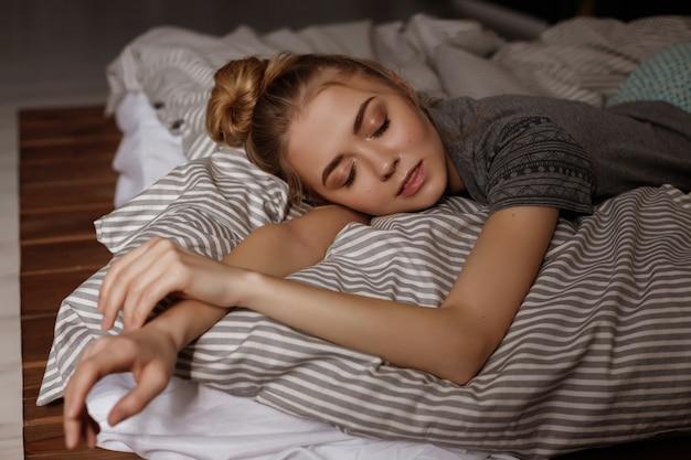 Dziewczyna śpi w łóżku w domu. niewyraźne miejsce. duży portret