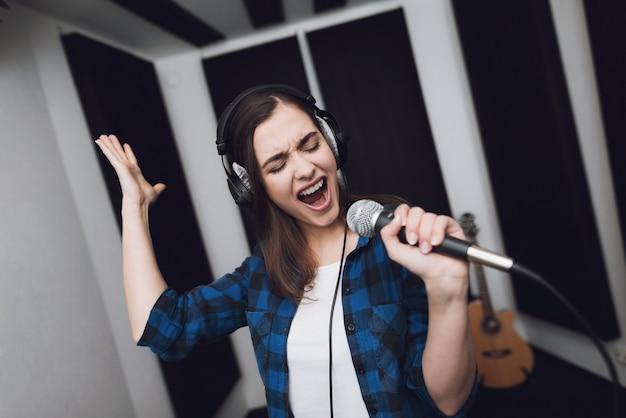 Dziewczyna śpiewa piosenkę w nowoczesnym studiu nagraniowym.
