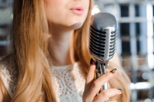 Dziewczyna śpiewa w mikrofonie retro