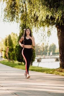 Dziewczyna sport fitness działa w pobliżu jeziora