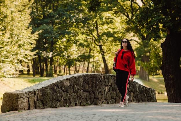 Dziewczyna sport fitness w moda sportowa spaceru w parku, sporty na świeżym powietrzu, styl miejski