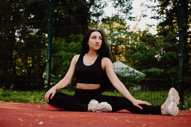 Dziewczyna sport fitness w odzieży sportowej moda robi ćwiczenia fitness jogi na ulicy, sporty na świeżym powietrzu, miejski styl