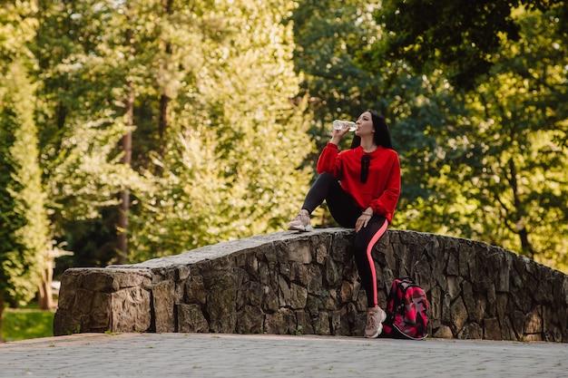 Dziewczyna sport fitness w wodzie pitnej sportowej mody, sporty na świeżym powietrzu, styl miejski
