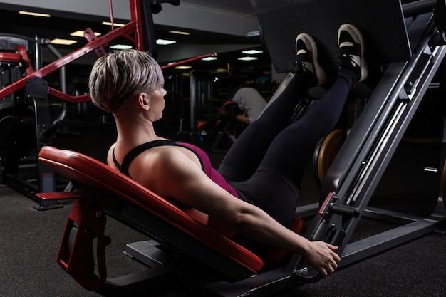 Dziewczyna sport jest zaangażowana na symulatorze w siłowni
