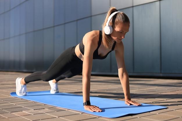 Dziewczyna sport robi deski ćwiczenia na świeżym powietrzu w ciepły letni dzień.