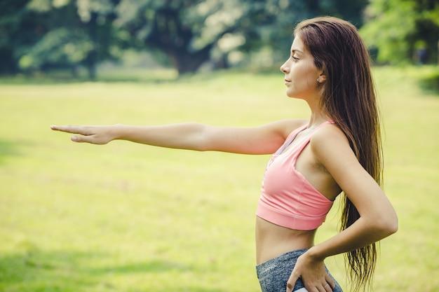 Dziewczyna sport rozciąganie ramienia na rozgrzewkę mięśni ciała przed i po ćwiczeniach widok z boku na zewnątrz