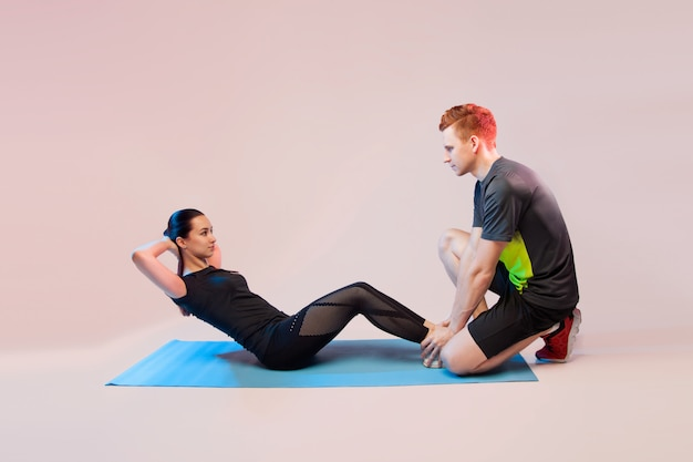 Dziewczyna sportowa i facet robi ćwiczenia. pomaga dziewczynie wstrząsnąć prasą.