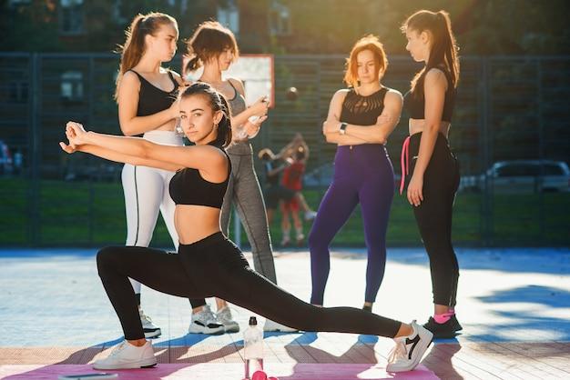 Dziewczyna sportowa robi sznurkiem na symulatorze na zewnątrz. kobieta lekkoatletycznego rozciąganie na zewnątrz przed treningiem w ciepły letni poranek.