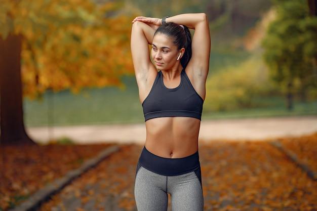 Dziewczyna sportowa w czarnym top szkolenia w parku jesienią