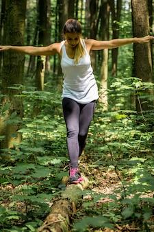 Dziewczyna sportowa w lesie na ścieżce, rozgrzewka przed bieganiem, sport