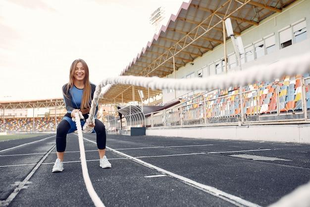 Dziewczyna sportowa w niebieskim mundurze szkolenia na stadionie z liny