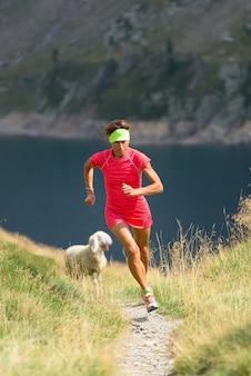 Dziewczyna sportsmenka na górskiej ścieżce z owcami w pobliżu