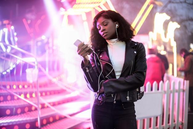 Dziewczyna sprawdza jej telefon podczas gdy chodzący w lunapark