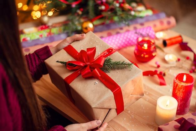 Dziewczyna sprawdza prezent po zapakowaniu przygotowywanie prezentów dla przyjaciół i krewnych w wigilię