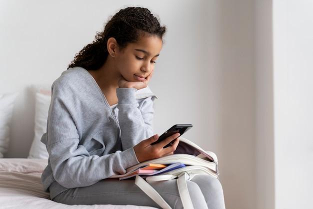Dziewczyna sprawdza swój telefon przed szkołą