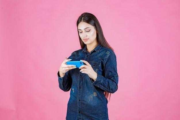 Dziewczyna sprawdza swoje wiadomości lub platformę społecznościową na swoim smartfonie