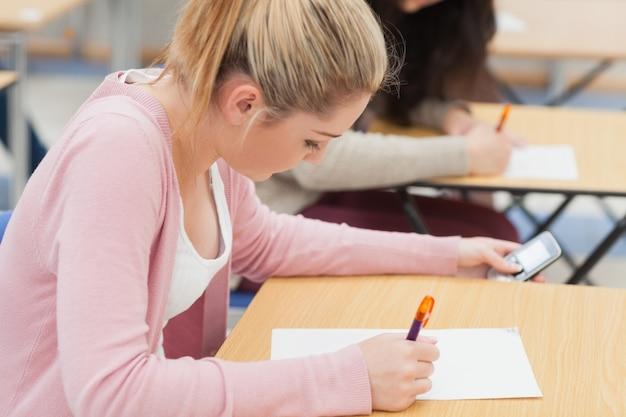Dziewczyna sprawdza telefon podczas egzaminu