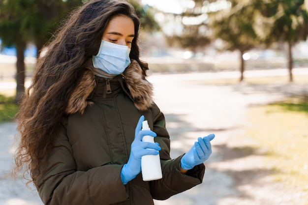 Dziewczyna spryskuje dłoń środkiem antyseptycznym do dezynfekcji