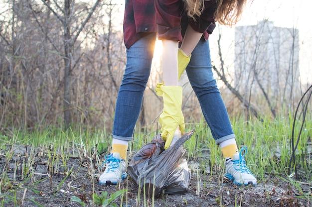 Dziewczyna sprząta w parku, podnosi plastikową butelkę i wrzuca ją do worka na śmieci