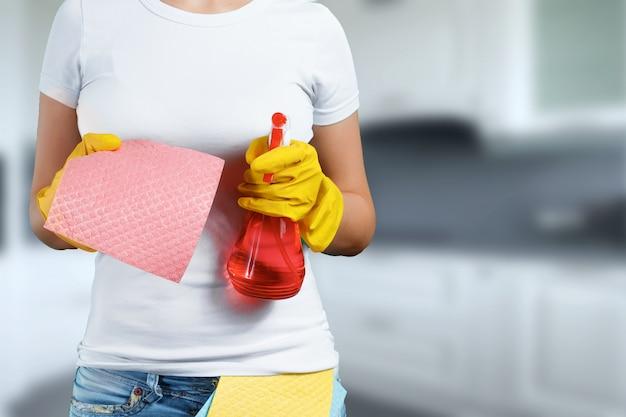 Dziewczyna sprzątaczka z środkiem czyszczącym w rękawiczkach i szmatą na rozmytym tle