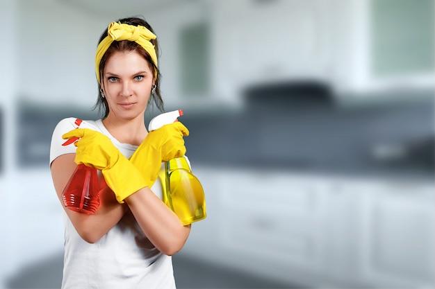 Dziewczyna sprzątaczka z środkiem czyszczącym w rękawiczkach i szmatce