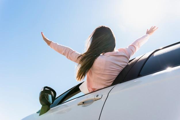 Dziewczyna stawia jej głowę z okno samochodu
